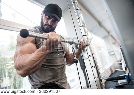 Muscle Training Concentration Of Sport Young Bearded Caucasian Male Lifting Heavy Weight In Fitness