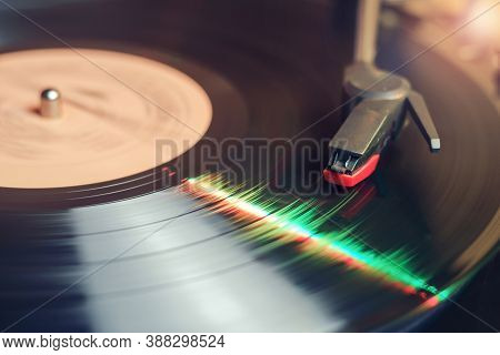 Retro Record Player With A Spinning Black Vinyl Record Reflecting Green And Red Lights