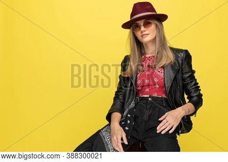 Bossy fashion model wearing hat and sunglasses while sitting on a chair on yellow studio background