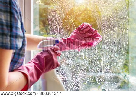 A Woman Clean A Window Pane With A Rag And Soap Suds. Cleaning With A Detergent. Hands In Pink Prote