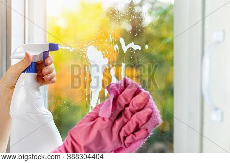 Hands In Pink Protective Gloves Washing Glass On The Windows Of The House With A Spray Bottle. A Wom
