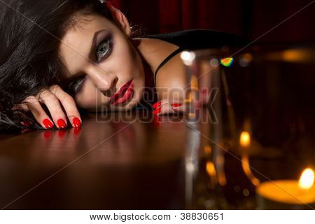 Fashion shoot of lonely young sexy woman with a candle