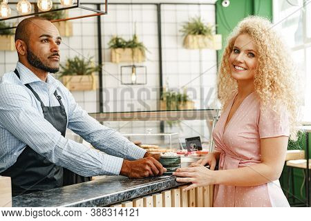 African American Man Worker Of A Coffee Shop Serving A Woman Customer