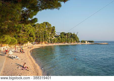Makarska, Croatia - September 5, 2019: Unidentified people rest at the beautiful beach at Adriatic Sea in Makarska Riviera, Dalmatia, Croatia