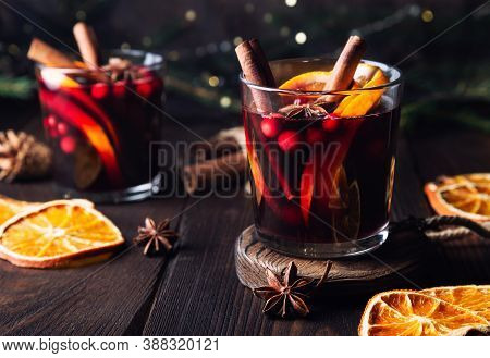 Christmas Mulled Wine With Cranberries, Orange And Spices On Rustic Wooden Background. Traditional H