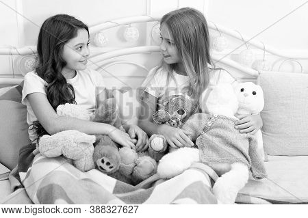 Sisters Unite. Little Sisters Play Toys In Bed. Small Sisters Relax Before Nap Time. Adorable Sister