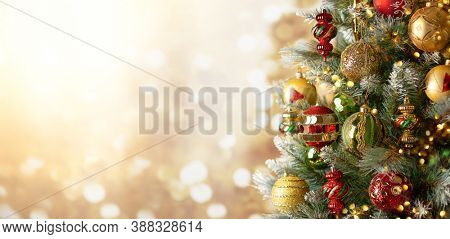 Christmas Tree with colourful Baubles and Decorations. Festive Christmas or New Year concept with bright bokeh and copy space.