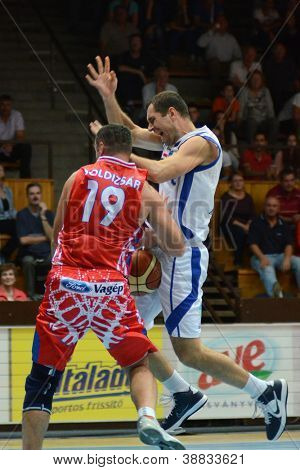 KAPOSVAR, HUNGARY - OCTOBER 20: Marco Spica (in white) in action at Hungarian Championship basketball game with Kaposvar (white) vs. Nyiregyhaza (red) on October 20, 2012 in Kaposvar, Hungary.