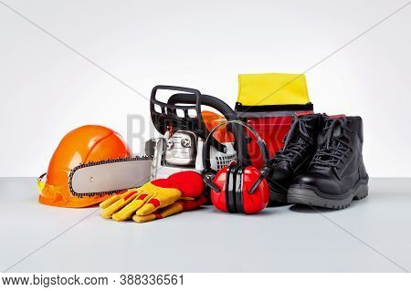 Chainsaw And Protective Clothes Of Lumberjack On Grey Surface.