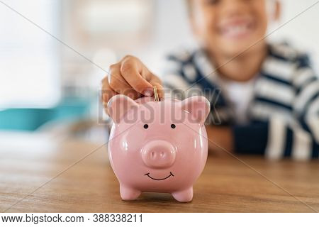 Close up of little boy saving coin into piggy bank at home. Closeup of child hand putting penny coin in piggy bank on table. Kid saving money by adding coin in pig shaped bank.