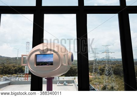 Modern Telescope In Front Of Wide Windows And Mountain View