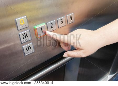 Woman's Hand Pressing On Elevator Button With Light Up Inside Elevator