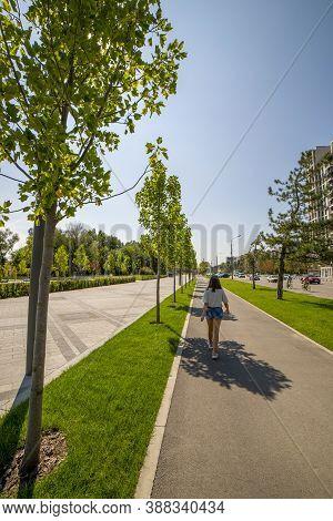 Dnepr, Ukraine - August 26, 2020: A Girl Walks Along An Alley On The Embankment Of The City