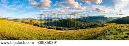 Mountainous Countryside Landscape. Panorama Of A Grassy Rural Field On The Hill. Village In The Dist