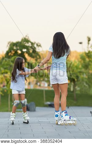 Happy Mother And Her Little Daughter Rollerskating In Summer Park