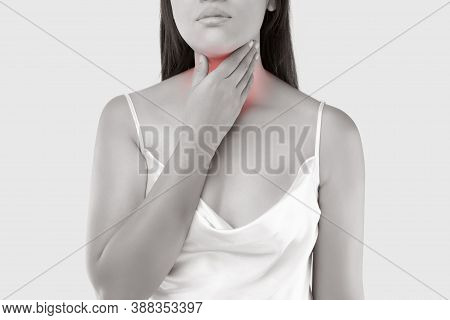 A Woman With A Pain In Her Throat On A Light Gray Background. Sore Throat Due To Virus Outbreak.
