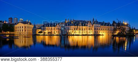 Panorama of the Binnenhof House of Parliament and Mauritshuis museum and the Hofvijver lake illuminated in the night. The Hague, Netherlands