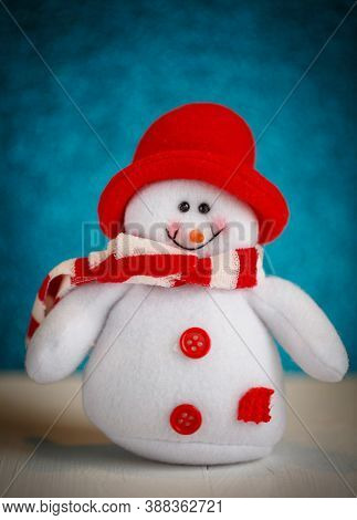 Smiling Snowman Toy Dressed In Scarf And Cap.