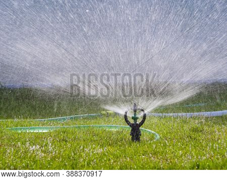 Sprinkler Splashing The Water To Green Grass Field, Select Focus Shallow Depth Of Field
