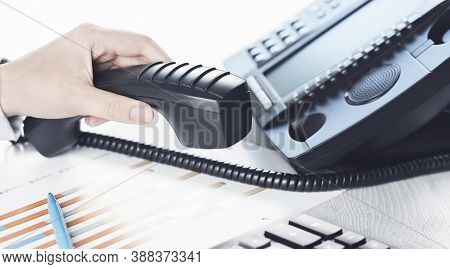 Business Communications. Finance Graphs. Using Voip Phone. Office, Close Up Of Hand With Receiver. C