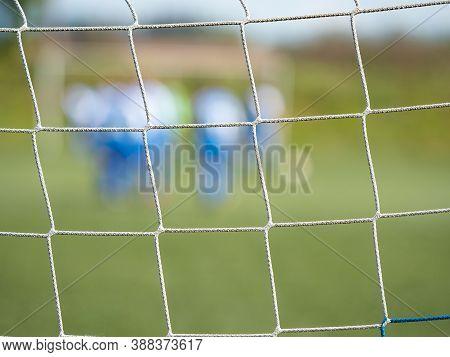 Look Through Net To Football Field In Soccer Stadium. Soccer Field With Green Grass In Football Spor