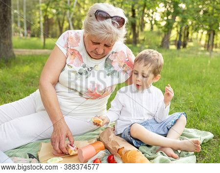 Small Boy With Grandmother Having Picnic In Nature At Sunset. Grandmother Spend Time In Holiday With