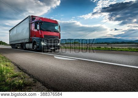 Red Semi Trailer Lorry Truck Passing On A Highway Driving At Beautiful Dramatic Sunset. Transportati
