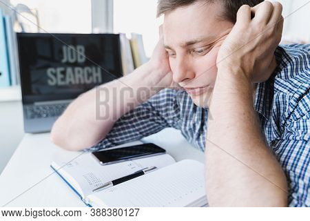 Man Holds Head With Hands On Table With Laptop. Unemployment,crisis,stress,job Loss.looking For Remo