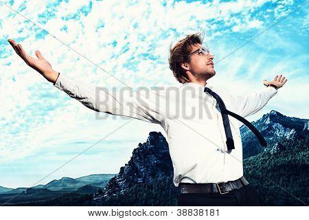 Erfolgreicher Geschäftsmann, stehend auf einem Gipfel des Berges und gezielt wegsehen.