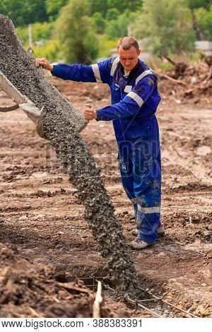 Construction Worker Laying Cement Or Concrete Into The Foundation Formwork