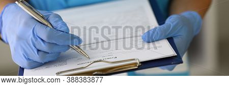 Doctors Gloved Hands Hold Clipboard With Pen And Patient Registration Document. Patient Registration