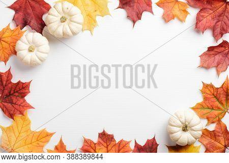 Autumn Leaves And Pumpkins Border Frame On White Table. Seasonal Background. Autumn Fall, Thanksgivi