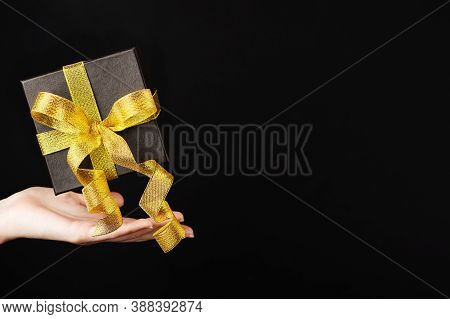 A Black Box With A Golden Ribbon On A Dark Background Levitates Over A Womans Hand. Gift Box For Gif