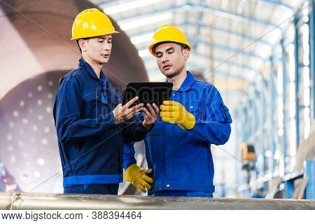 Asian experts checking information on tablet PC while supervising work in a modern factory