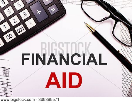 On The Reports There Is A Calculator, Glasses, A Pen And A Notebook With The Inscription Financial A