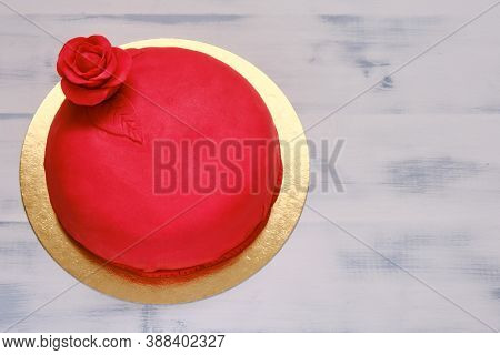 Red Cake Covered With Marzepan Or Mastic And Decorated With A Flower, Copy Space, Background