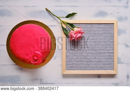 Red Cake Covered With Marzepan Or Mastic With A Flower On A White Background, Copy Space, Background