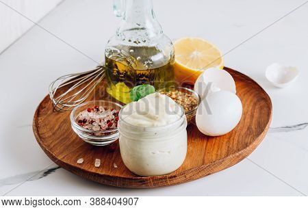 Homemade Mayonnaise Sauce With Ingredient - Olive Oil, Eggs, Mustard And Lemon On A Wooden Plate.