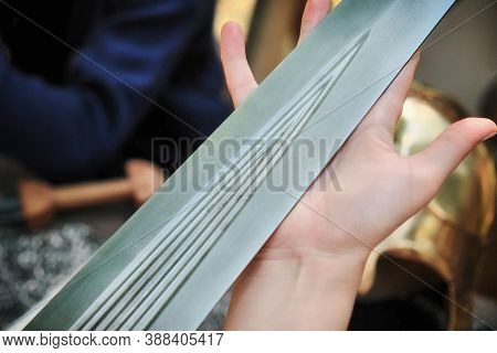 Close-up Ancient Roman Sword Blade In The Woman's Hand. The Girl Holds The Sword In Her Palm, Close-