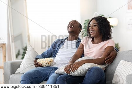 Laughing African American Family Of Two Watching Movie Together At Home, Eating Popcorn, Copy Space.