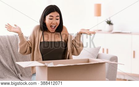 Excited Asian Lady Customer Receive Good Parcel, Opening Cardboard Box At Home, Satisfied With Great