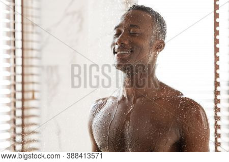 Happy African Man Taking Cold Shower Refreshing In The Morning, Washing Body Standing Under Falling