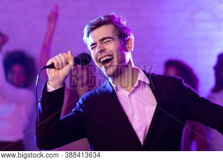 Talented Singer Guy On Karaoke Party Singing Song Having Fun In Night Club Indoor. Low Light