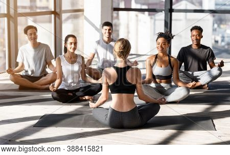 Group Of Young Multhiethnic People Practicing Yoga With Instructor During Group Lesson, Sitting Toge