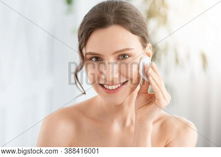 Smiling Pretty Young Woman Cleaning Her Face, Using Cotton Pads And Cleansing Product, Closeup. Youn