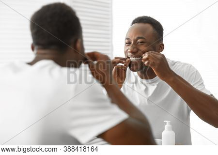 Black Man Cleaning Teeth With Floss Standing Near Mirror In Bathroom At Home In The Morning. Healthy