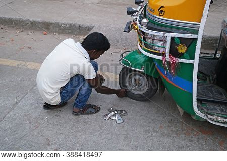 KUMROKHALI, INDIA - FEBRUARY 24, 2020: Mechanic in the workshop repairs tuk tuk, Kumrokhali, West Bengal, India