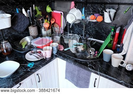 Dirty Dishes In The Kitchen Sink And On The Countertop. Not Done Household Chores In The Kitchen. A