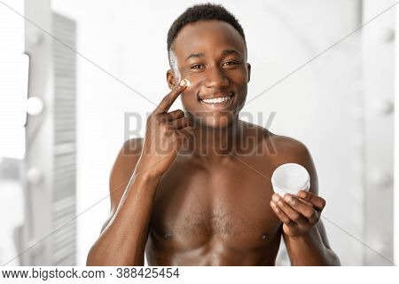 Male Facial Skincare. Cheerful African Guy Applying Cream On Face Holding Moisturizer Jar, Smiling T