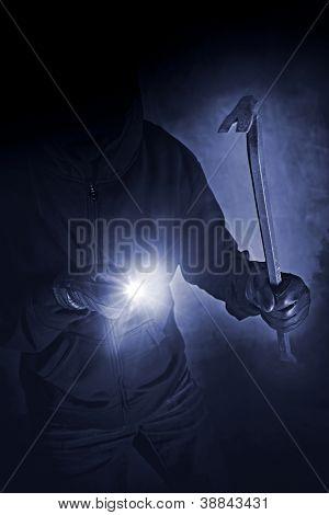 Unrecognizable burglar with crowbar and flashlight.